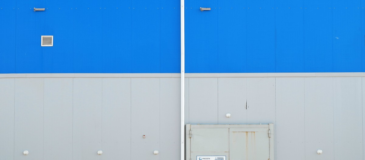 blue ad white wall ouside industrial building