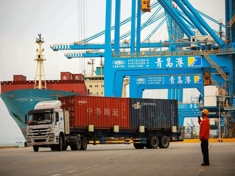 A staff member watches over a truck as he talks on his interphone at a port in Qingdao, east China's Shandong province on November 8, 2018. - China's exports to the US and the rest of the world grew more than expected in October, official data showed on November 8, as its traders apparently rushed shipments across the Pacific ahead of higher tariffs. (Photo by STR / AFP) / China OUT        (Photo credit should read STR/AFP via Getty Images)